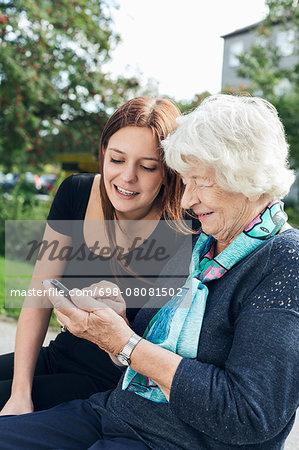 Young woman looking at grandmother using smart phone at park
