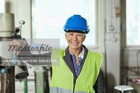 Portrait of happy mature female worker wearing hardhat in factory