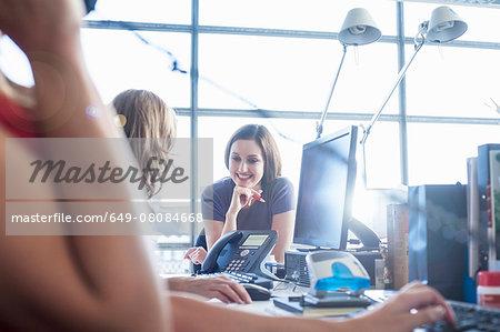 Businesswomen chatting at office desk