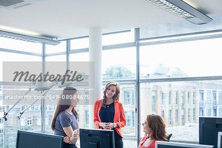 Three businesswomen discussing ideas at office desk