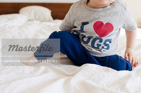 Cropped shot of baby girl wearing pyjamas sitting up in bed