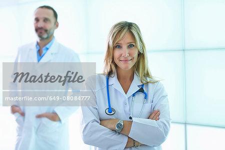 Doctors posing against backlit wall panel