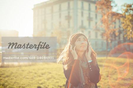 Mid adult woman listening to headphones in sunlit park