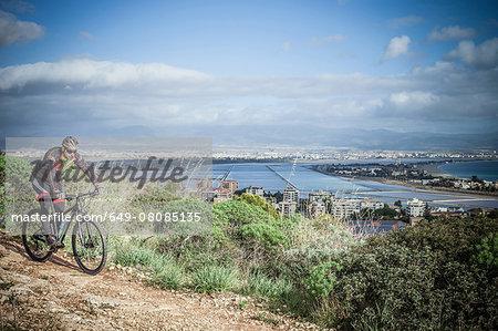 Male mountain biker speeding downhill on coastal path, Cagliari, Sardinia, Italy