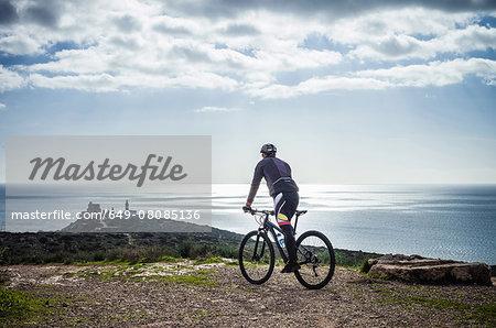 Silhouetted view of male mountain biker on coastal path, Cagliari, Sardinia, Italy