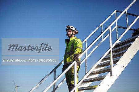 Portrait of engineer on steps, at wind farm