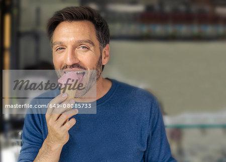 Portrait of mature man licking ice cream cone