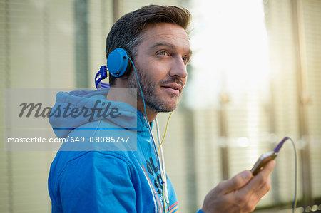 Mature man on city street choosing headphone music on smartphone