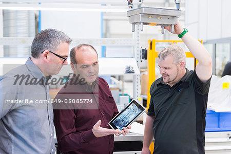 Engineering team looking at digital tablet in factory