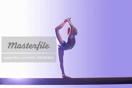 Young gymnast performing on balance beam