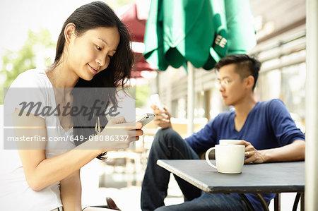 Tourist couple at sidewalk cafe using smartphones, The Bund, Shanghai, China