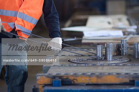 Factory worker bending metal rod in concrete reinforcement factory
