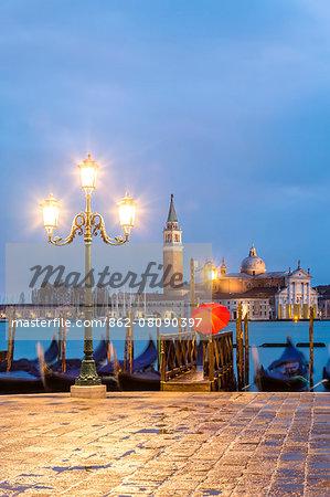 Italy, Veneto, Venice. Woman with red umbrella on Riva degli Schiavoni at dawn (MR)
