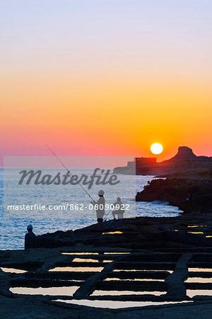 Mediterranean Europe, Malta, Gozo Island, Xwejni Bay, fisherman at the salt pans at sunrise
