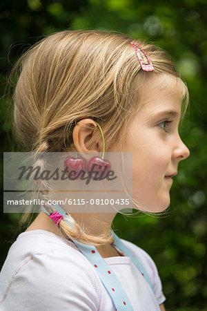 Little girl, cherries dangling from her ears
