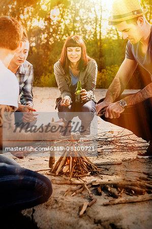 Group of friends lighting campfire on a riverbank, Osijek, Croatia