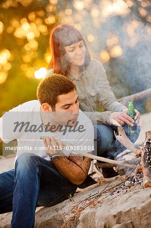 Young man arranging firewood at campfire, girlfriend in background, Osijek, Croatia
