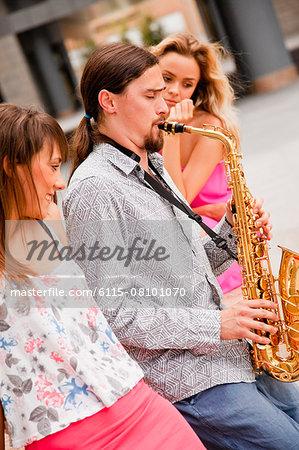 Man playing the saxophone to women, Osijek, Croatia