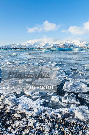Mountains behind the frozen water of Jokulsarlon Iceberg Lagoon, Jokulsarlon, south east Iceland, Polar Regions