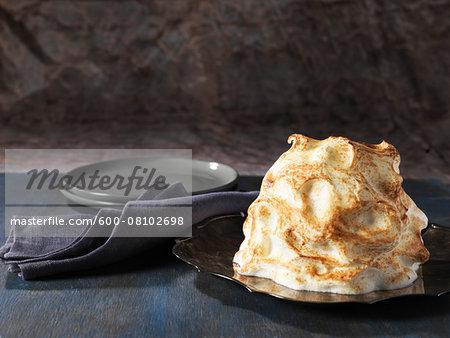 Baked Alaska, golden meringue on black plate with grey napkin, studio shot on grey background