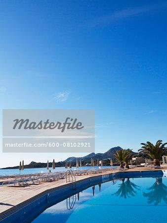 Sunbeds and Closed Sunshades on Deck by Pool at Hotel, Cala Ratjada, Majorca, Balearic Islands, Spain