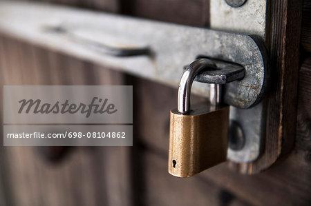 Padlock attached to wooden door