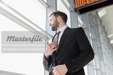 Businessman adjusting tie in airport