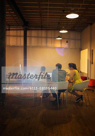 Business people at laptop preparing audio visual presentation