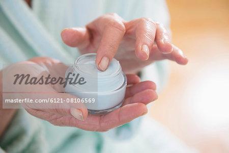 Senior woman applying moisturizer, Munich, Bavaria, Germany
