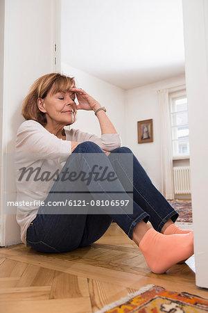 Senior woman sitting at the doorway and thinking, Munich, Bavaria, Germany