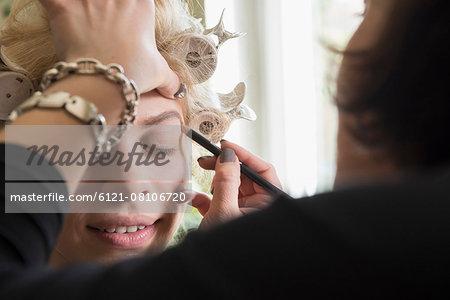 Makeup artist applying eyebrow make up, Munich, Bavaria, Germany