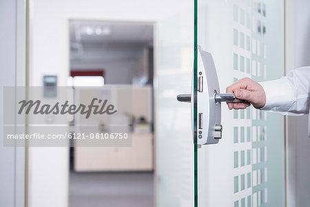 Businessman opening office door, Munich, Bavaria, Germany