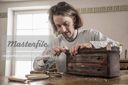 Carpenter carving on an antique bone box at workshop, Bavaria, Germany