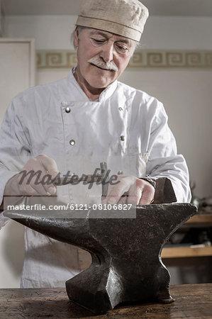 Senior craftsman shaping of copper ring at workshop, Bavaria, Germany