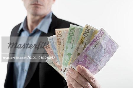 Businessman showing euro banknotes, Bavaria, Germany
