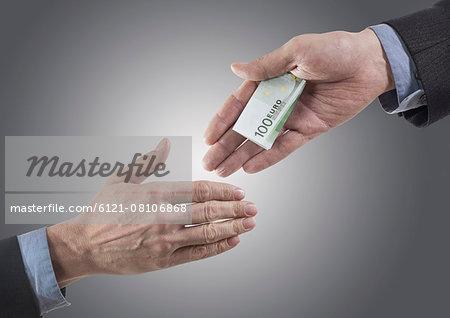 Businessman holding out bribing cash with handshake, Bavaria, Germany