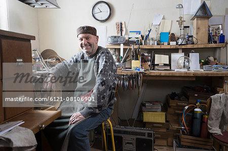 Senior male goldsmith smiling in workshop, Bavaria, Germany