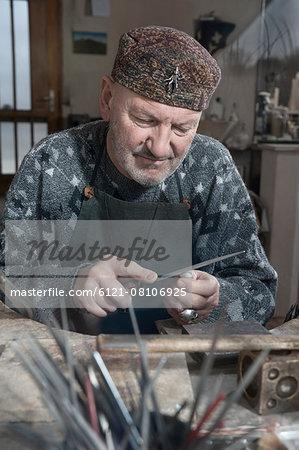 Senior male goldsmith shaping crystal with rasp in workshop, Bavaria, Germany