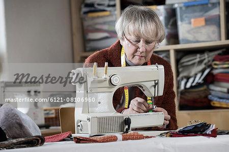 Senior female fashion designer stitching in workshop, Bavaria, Germany