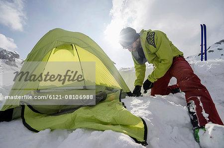 Man constructing tent in snow, Tyrol, Austria