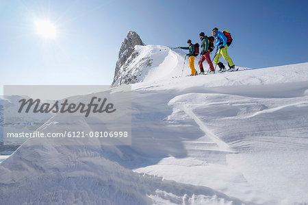 Ski mountaineers climbing on snowy peak, Tyrol, Austria