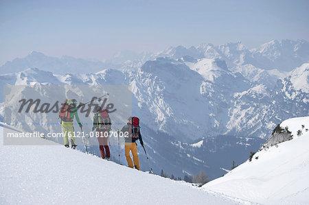 Ski tourers looking at mountains view, Tyrol, Austria