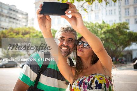 Young woman and mature man taking smartphone selfie, Copacabana, Rio De Janeiro, Brazil