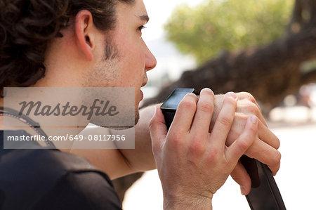 Over the shoulder view of young man using smartwatch, Copacabana, Rio De Janeiro, Brazil