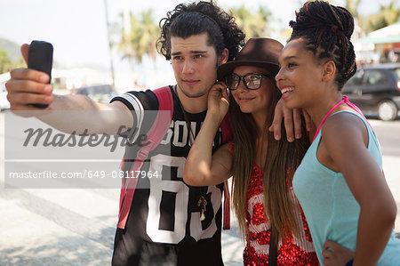 Three young adult friends taking smartphone selfie, Copacabana, Rio De Janeiro, Brazil