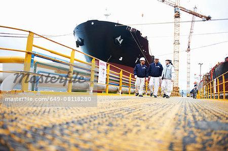 Three workers at shipping port, low angle view, GoSeong-gun, South Korea