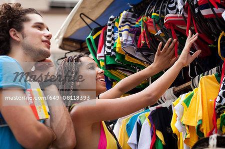 Tourist couple browsing market stall, Copacabana town, Rio De Janeiro, Brazil