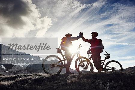 Mountain bikers shaking hands, Valais, Switzerland