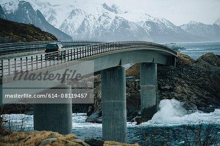Off road vehicle crossing coastal bridge, Reine, Lofoten, Norway