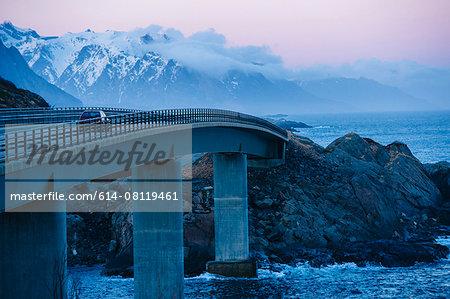 Vehicle crossing coastal bridge at dusk, Reine, Lofoten, Norway